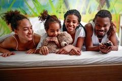 Familia afroamericana joven sonriente que ve la TV junto imagen de archivo libre de regalías