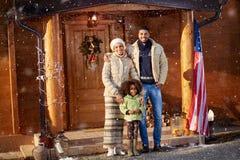 Familia afroamericana que coloca la casa de madera delantera Imagen de archivo libre de regalías