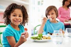 Familia afroamericana que come la comida en casa junto Foto de archivo
