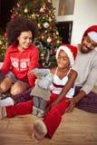 Familia afroamericana que intercambia los regalos delante de la Navidad t fotos de archivo libres de regalías