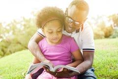 Familia afroamericana que lee un libro junto en el parque al aire libre imagenes de archivo