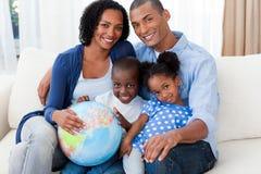 Familia afroamericana que sostiene un globo terrestre fotografía de archivo libre de regalías