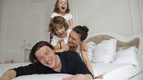 Familia agitada y activa que juega junto en una cama en casa durante Weeked Los padres jovenes con sonrisas encantadoras son almacen de video