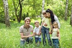 Familia al aire libre con los cabritos en hierba verde. Foto de archivo
