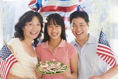 Familia al aire libre en el cuarto de julio con los indicadores Foto de archivo libre de regalías