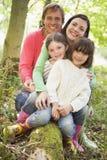 Familia al aire libre en las maderas que se sientan en la sonrisa del registro Fotos de archivo libres de regalías