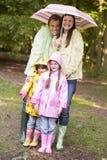Familia al aire libre en lluvia con la sonrisa del paraguas Fotos de archivo libres de regalías