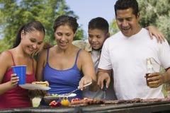 Familia alegre alrededor de la parrilla en la comida campestre Foto de archivo libre de regalías