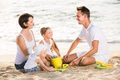 Familia alegre con dos niños que juegan en la playa imagen de archivo libre de regalías
