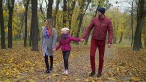 Familia alegre con la muchacha que camina en parque del otoño almacen de metraje de vídeo