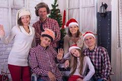 Familia alegre con los amigos, en los sombreros de Papá Noel Imágenes de archivo libres de regalías