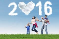 Familia alegre con los números 2016 en el campo Fotos de archivo libres de regalías