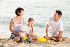Familia alegre con los niños que juegan en la playa Fotos de archivo