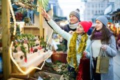 Familia alegre de tres en el mercado de la Navidad Fotos de archivo libres de regalías