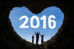 Familia alegre dentro de la cueva con los números 2016 Fotos de archivo