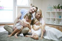 Familia alegre en casa mirada de la cámara foto de archivo libre de regalías