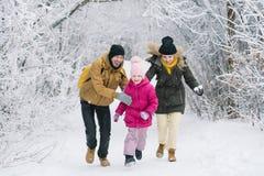 Familia alegre en el bosque que juega bolas de nieve Imagen de archivo