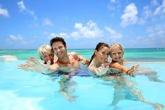 Familia alegre en piscina del infinito Foto de archivo libre de regalías