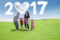 Familia alegre funcionada con en el campo con 2017 Fotos de archivo libres de regalías