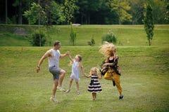 Familia alegre Las muchachas, la mujer y el hombre sonríen en paisaje del verano foto de archivo