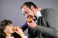 Familia alegre que come las frutas sanas Fotografía de archivo