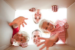 Familia alegre que desempaqueta los rectángulos fotografía de archivo