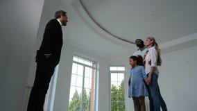 Familia alegre que habla con el agente que muestra la nueva casa metrajes
