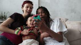 Familia alegre que hace el selfie con el teléfono elegante almacen de video