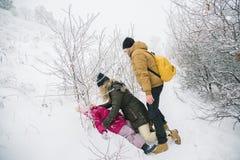 Familia alegre que juega en nieve en invierno Fotos de archivo