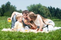 Familia alegre que merienda en el campo Imagenes de archivo
