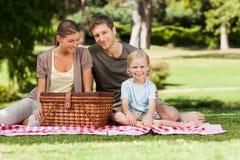 Familia alegre que merienda en el campo en el parque Fotos de archivo libres de regalías