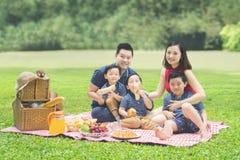 Familia alegre que merienda en el campo junto en el parque Fotos de archivo libres de regalías