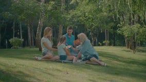 Familia alegre que merienda en el campo en parque del verano almacen de metraje de vídeo