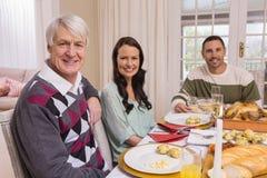 Familia alegre que mira la cámara durante cena de la Navidad Foto de archivo