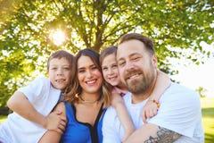 Familia alegre que plantea el abarcamiento en verano Foto de archivo