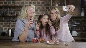 Familia alegre que presenta para el selfie en la tabla de cocina almacen de video
