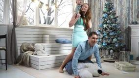 Familia alegre que salta cerca del árbol de navidad almacen de metraje de vídeo