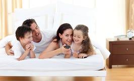 Familia alegre que se divierte en el dormitorio Foto de archivo libre de regalías