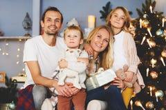 Familia alegre que se sienta en la sala de estar Foto de archivo