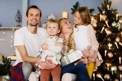 Familia alegre que se sienta en la sala de estar Imagenes de archivo