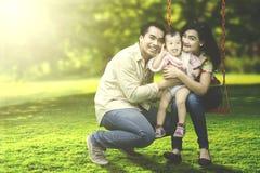Familia alegre que sonríe en el oscilación Imagen de archivo libre de regalías
