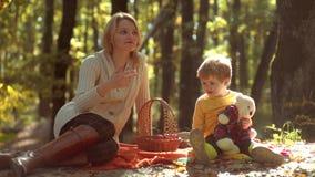 Familia alegre que tiene comida campestre que se relaja junto en la naturaleza amarilla del otoño en parque Madre e hijo sonrient almacen de video