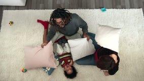 Familia alegre que tiene lucha de almohada en el piso almacen de metraje de vídeo