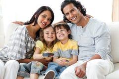 Familia alegre que ve la TV junto Foto de archivo