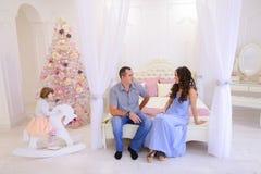 Familia alegre recolectada para intercambiar los regalos de la Navidad en s brillante Imagen de archivo