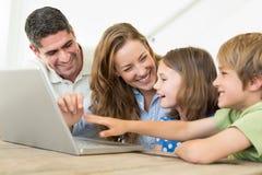 Familia alegre usando el ordenador portátil fotografía de archivo