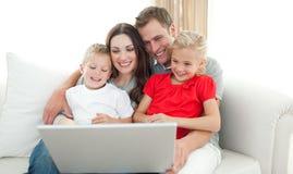 Familia alegre usando un ordenador que se sienta en el sofá Fotografía de archivo libre de regalías