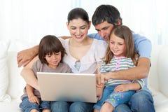 Familia alegre usando una computadora portátil en el sofá Fotos de archivo