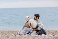 Familia alternativa con una señora un hombre y un perro junto en la playa que disfruta de una comida campestre en amistad y parte fotografía de archivo libre de regalías