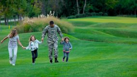 Familia americana con el soldado de los E.E.U.U. del padre que juega en el césped del parque almacen de video